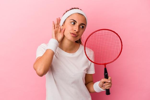 Jeune femme caucasienne blonde mignonne tenant une raquette de badminton isolée sur fond rose en essayant d'écouter un commérage.
