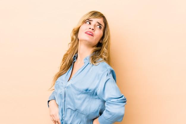 Jeune femme caucasienne blonde souffrant de maux de dos.