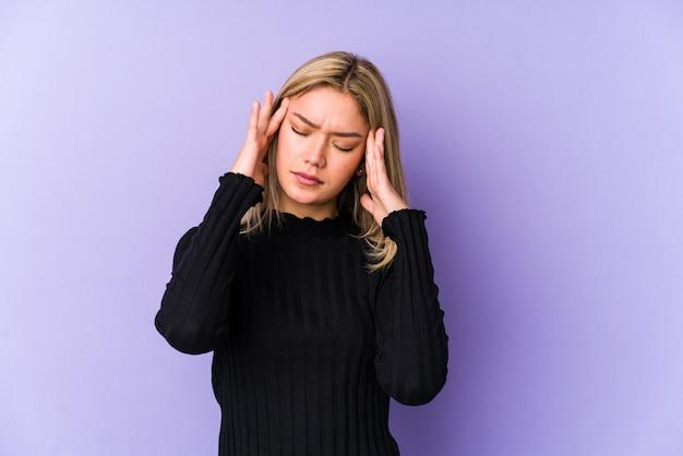 Jeune femme caucasienne blonde toucher les tempes et avoir des maux de tête.