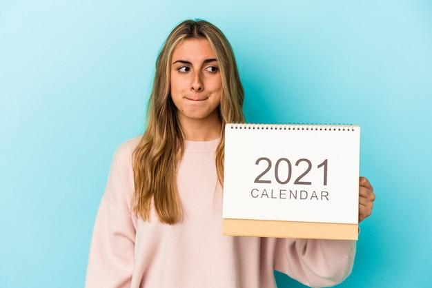 Jeune femme caucasienne blonde trouant un calendrier isolé confus, se sent douteux et incertain.