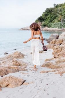 Jeune femme caucasienne calme et heureuse avec ukulélé sur la plage rocheuse tropicale au coucher du soleil