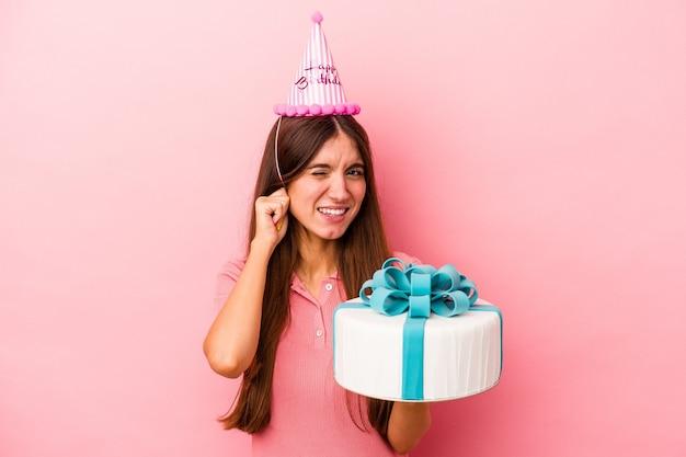 Jeune femme caucasienne célébrant un anniversaire isolé sur fond rose couvrant les oreilles avec les mains.