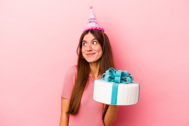 Jeune femme caucasienne célébrant un anniversaire isolé sur fond rose rêvant d'atteindre des objectifs et des objectifs
