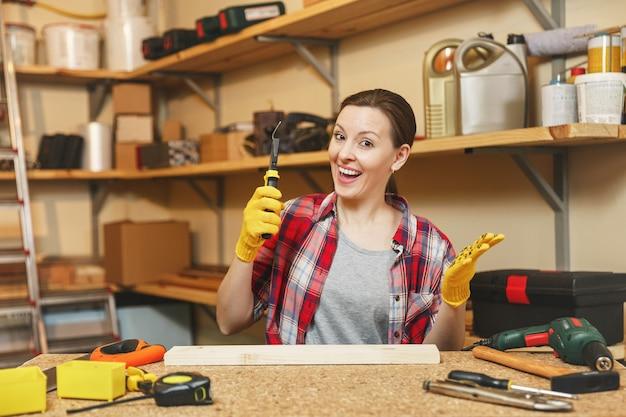 Jeune femme caucasienne en chemise à carreaux, t-shirt gris, gants jaunes travaillant dans un atelier de menuiserie sur une table en bois avec différents outils, enlevant le clou avec une pince après avoir enfoncé le panneau.