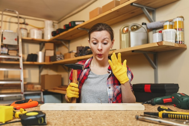 Jeune femme caucasienne en chemise à carreaux, t-shirt gris, gants jaunes travaillant dans un atelier de menuiserie sur une table en bois avec différents outils, martelant des clous dans une planche avec un marteau, clou courbé.