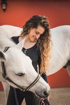 Jeune femme caucasienne avec un cheval dans un centre équestre