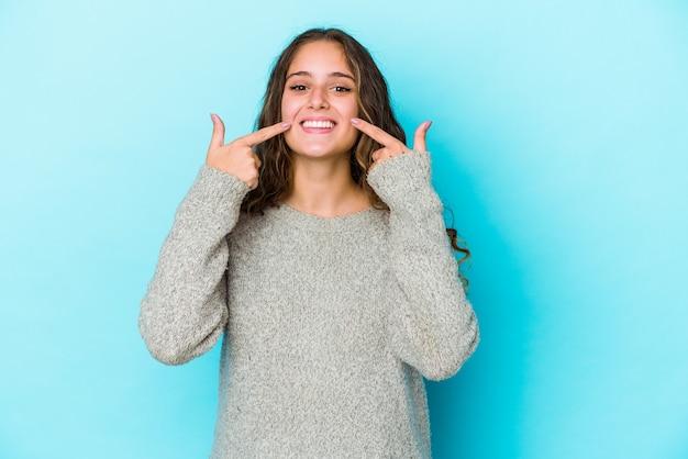 Jeune femme caucasienne cheveux bouclés sourires isolés, pointant du doigt la bouche.