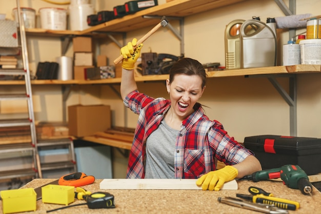 Jeune femme caucasienne en colère agressive en chemise à carreaux, t-shirt gris, gants jaunes travaillant dans un atelier de menuiserie sur une table en bois avec différents outils, martelant des clous dans une planche avec un marteau.