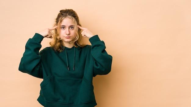 Jeune femme caucasienne concentrée sur une tâche, gardant l'index pointant la tête.