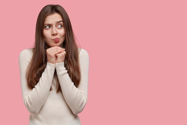 Une jeune femme caucasienne contemplative garde les mains sous le menton, fait la moue, regarde de côté avec confusion