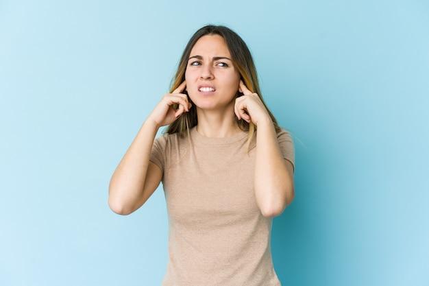 Jeune femme caucasienne couvrant les oreilles avec les doigts, stressée et désespérée par un bruit ambiant.