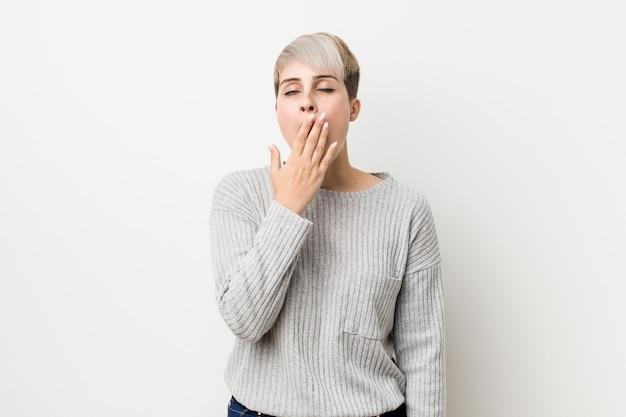 Jeune femme caucasienne curvy isolée sur blanc bâillant montrant un geste fatigué couvrant la bouche avec la main.