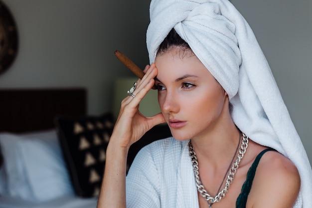 Jeune femme caucasienne dans la chambre d'hôtel en peignoir et serviette blanche sur avait avec cigare.