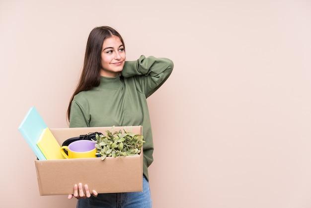 Jeune femme caucasienne déménageant dans une nouvelle maison isolée en touchant l'arrière de la tête, en pensant et en faisant un choix.