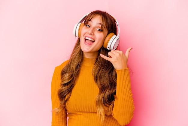 Jeune femme caucasienne écoutant de la musique avec des écouteurs isolés montrant un geste d'appel de téléphone portable avec les doigts.