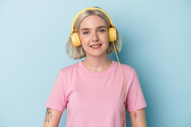Jeune femme caucasienne écoutant de la musique isolée sur fond bleu heureuse, souriante et joyeuse.