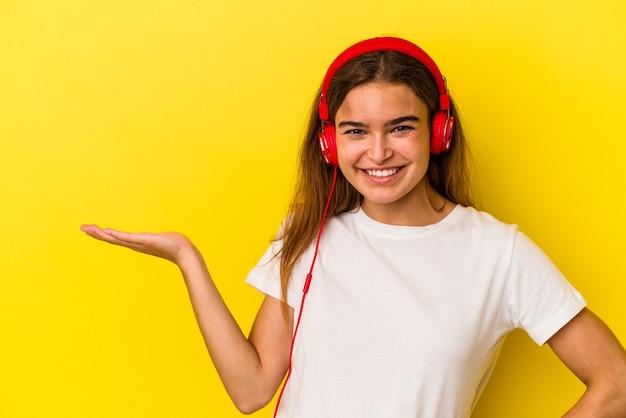 Jeune femme caucasienne écoutant de la musique isolée sur fond jaune montrant un espace de copie sur une paume et tenant une autre main sur la taille.