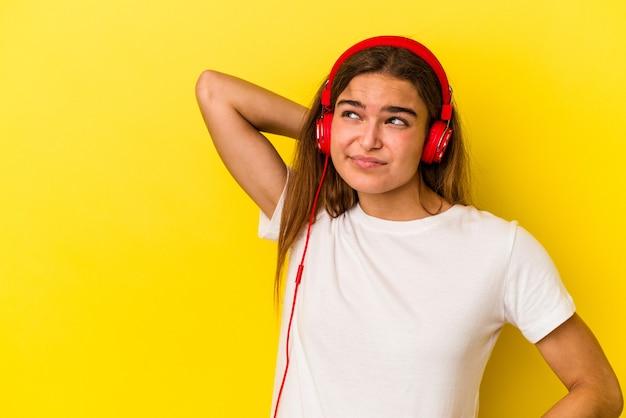 Jeune femme caucasienne écoutant de la musique isolée sur fond jaune touchant l'arrière de la tête, pensant et faisant un choix.
