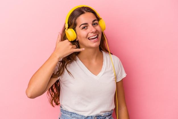 Jeune femme caucasienne écoutant de la musique isolée sur fond rose montrant un geste d'appel de téléphone portable avec les doigts.