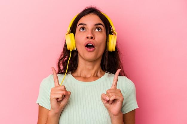 Jeune femme caucasienne écoutant de la musique isolée sur fond rose pointant vers le haut avec la bouche ouverte.