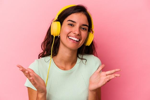 Jeune femme caucasienne écoutant de la musique isolée sur fond rose recevant une agréable surprise, excitée et levant les mains.