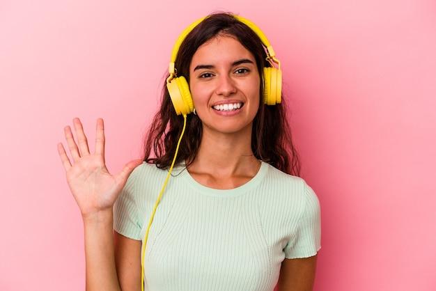 Jeune femme caucasienne écoutant de la musique isolée sur fond rose souriant joyeux montrant le numéro cinq avec les doigts.