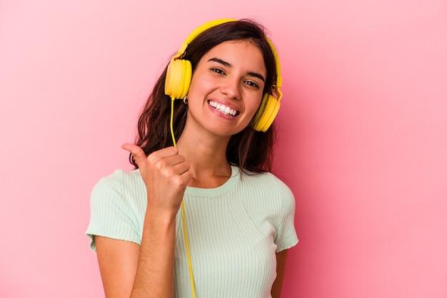 Jeune femme caucasienne écoutant de la musique isolée sur fond rose souriant et levant le pouce vers le haut