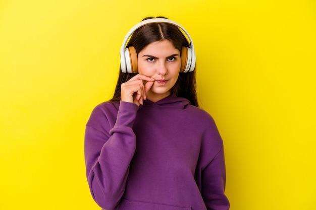 Jeune femme caucasienne, écouter de la musique avec un casque isolé sur un mur rose avec les doigts sur les lèvres en gardant un secret.