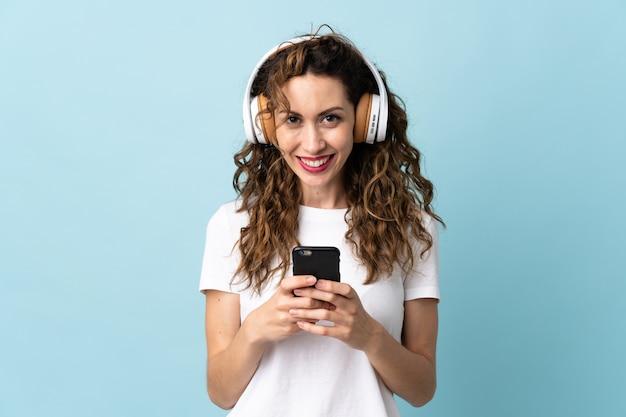 Jeune femme caucasienne, écouter de la musique avec un mobile