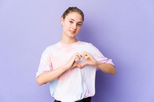 Jeune femme caucasienne sur l'espace violet souriant et montrant une forme de coeur avec les mains.