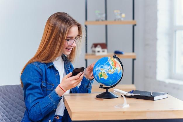 Jeune femme caucasienne est assise à la table et tourne le globe pour choisir le pays pour les vacances et prendre des notes dans le carnet de notes.