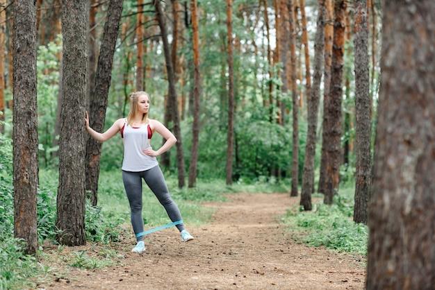 Jeune femme caucasienne exerce dans le parc parmi les arbres. sports de plein air.