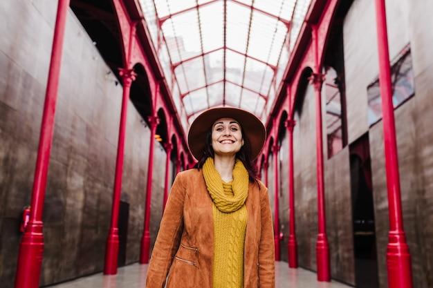 Jeune femme caucasienne à l'extérieur sur la construction de colonnes rouges. concept de voyage