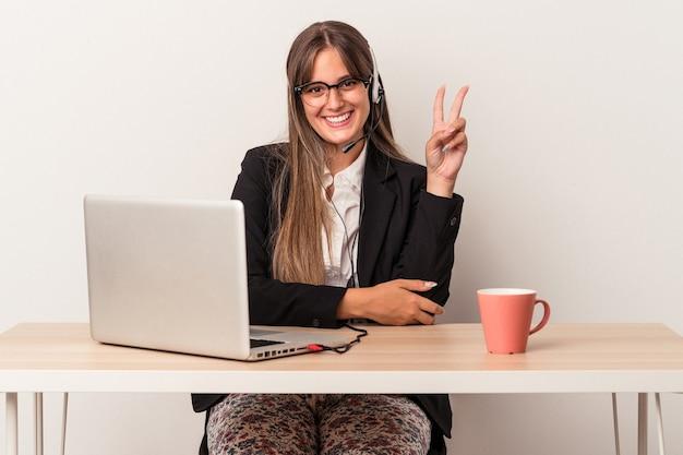 Jeune femme caucasienne faisant du télétravail isolé sur fond blanc montrant le numéro deux avec les doigts.