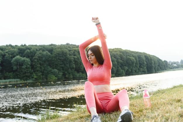Jeune femme caucasienne faisant un exercice d'entraînement actif sur un tapis de yoga près de la rivière en été. concept de mode de vie sain