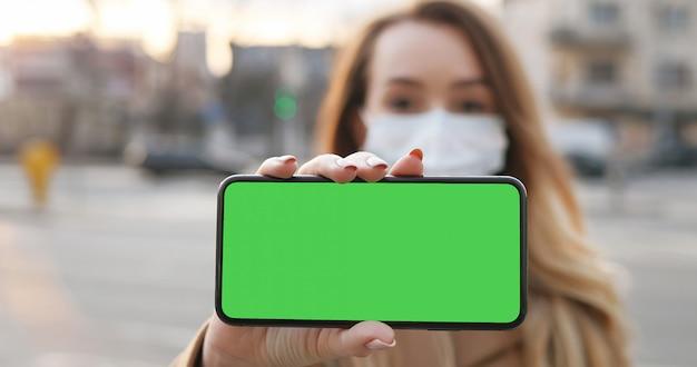 Jeune femme caucasienne floue dans un masque médical montrant un téléphone horizontal avec écran vert. fille avec protection antivirus démontrant smartphone avec incrustation en chrominance horizontalement en ville.