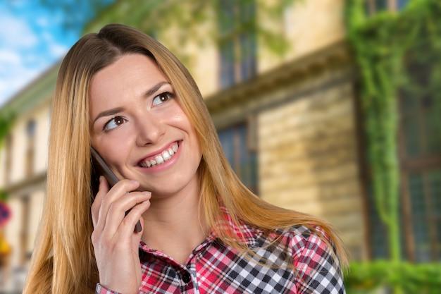 Jeune femme caucasienne heureuse appelle avec un téléphone portable