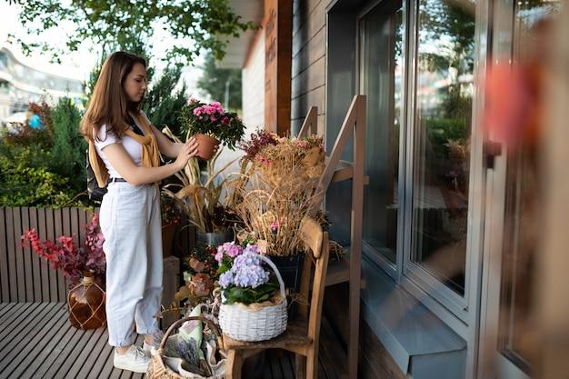 Une jeune femme caucasienne heureuse choisit des fleurs en pot à acheter à l'étal de jardin extérieur