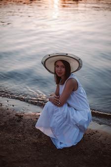 Une jeune femme caucasienne heureuse dans une robe d'été blanche et un chapeau est accroupie et étreint ses épaules sur ...