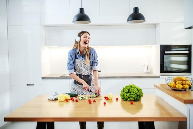 Jeune femme caucasienne heureuse en tablier debout dans la cuisine et couper le concombre tout en écoutant de la musique et du chant. sur le comptoir de la cuisine, il y a toutes sortes de légumes. concept d'alimentation saine.