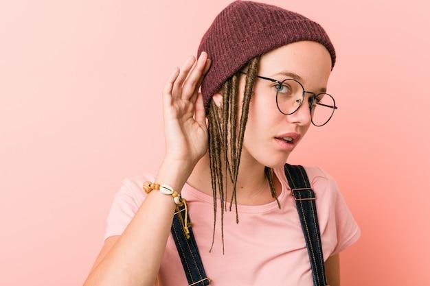 Jeune femme caucasienne hipster essayant d'écouter un potin.
