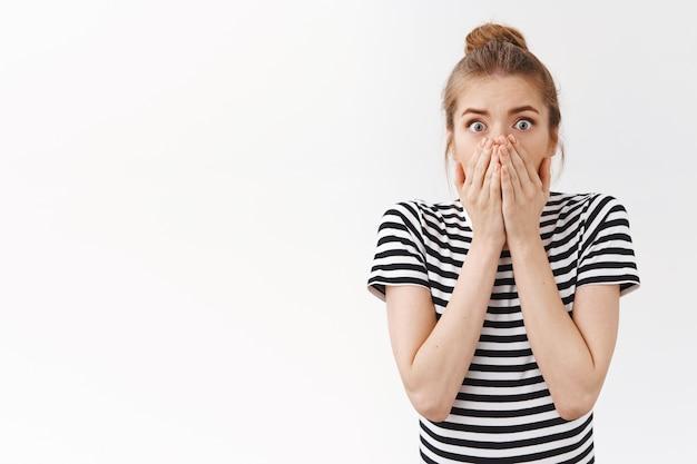 Une jeune femme caucasienne inquiète et choquée avec un petit pain en désordre, haletant en retenant son souffle abasourdi, couvre la bouche avec les mains et regarde la caméra effrayée pour toi, effrayée a causé un accident, fond blanc