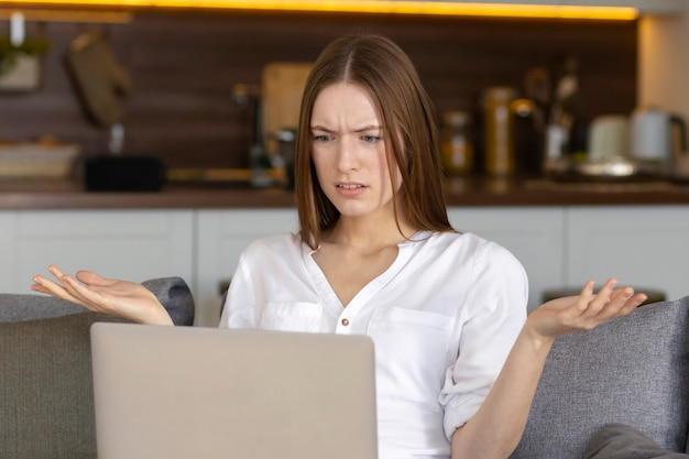 Jeune femme caucasienne insatisfaite regardant un écran d'ordinateur portable, lisant de mauvaises nouvelles dans un message ou ayant des pertes de données ou un problème avec un appareil cassé