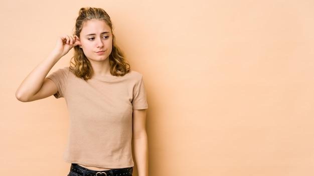Jeune femme caucasienne isolée sur beige couvrant les oreilles avec les doigts, stressée et désespérée par une forte ambiance.