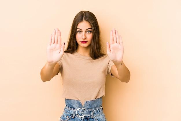 Jeune femme caucasienne isolée sur beige debout avec la main tendue montrant le panneau d'arrêt, vous empêchant.