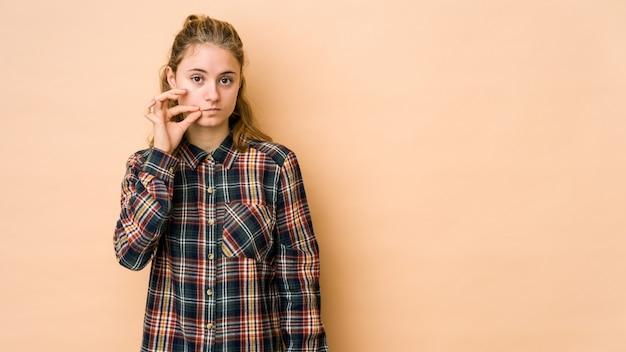 Jeune femme caucasienne isolée sur beige avec les doigts sur les lèvres gardant un secret.