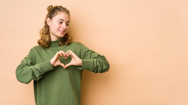 Jeune femme caucasienne isolée sur beige souriant et montrant une forme de coeur avec les mains.