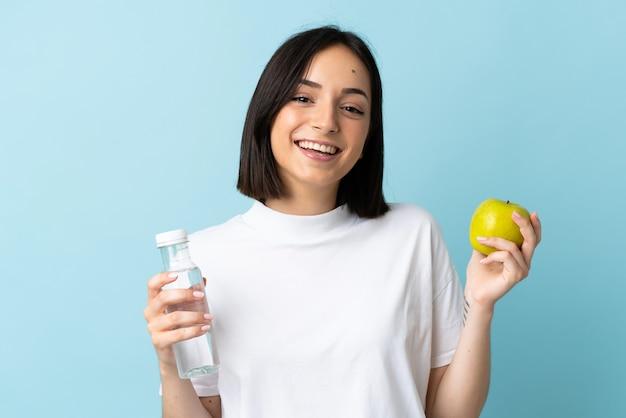 Jeune femme caucasienne isolée sur bleu avec une pomme et avec une bouteille d'eau