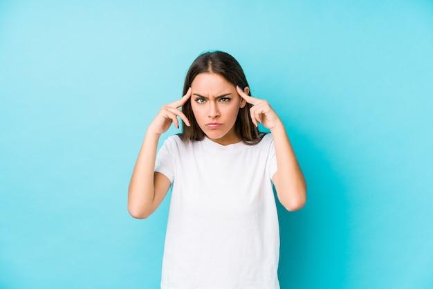 Jeune femme caucasienne isolée concentrée sur une tâche, gardant l'index pointant la tête.