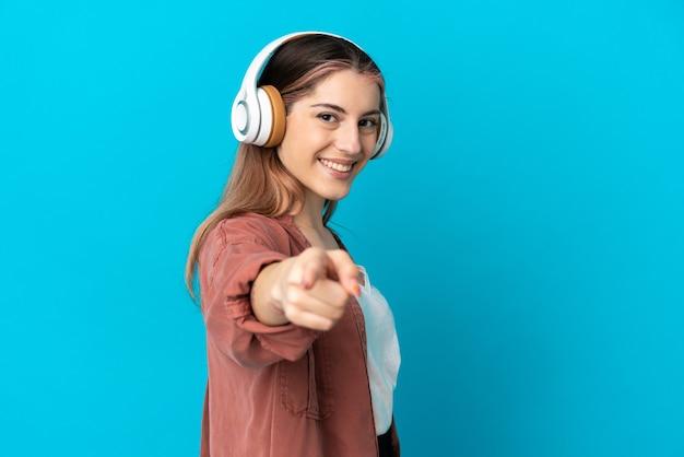 Jeune femme caucasienne isolée écoutant de la musique et pointant vers l'avant